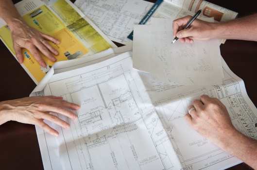 two sets of hands work over various house planning documents