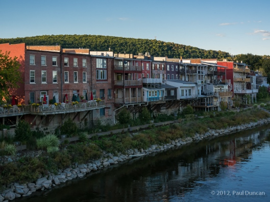 The backs of old brick and stone business buildings line up along the Susquehanna River.