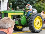 a boy and his dad drive a farm tractor