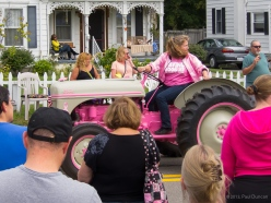 woman in pink on pink farm tractor