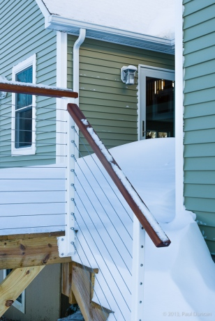 Snow drifts pile up against the house
