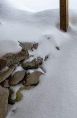 Snow drifts with rocks and wood post