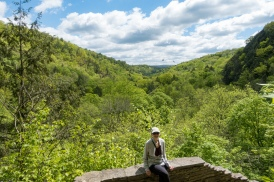 Lori relaxes on the Cliff Staircase with Enfield Glen receding in the distance and turkey vultures circling overhead