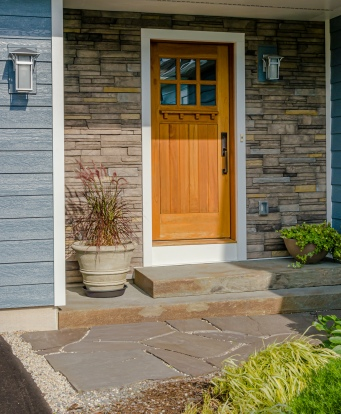 Stone facade replaced vinyl siding around front door.